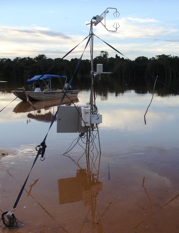 Pesquisadores do Cena estudam o desaparecimento do carbono da atmosfera. Instrumento instalado as margens do rio Araguaia e barco com a equipe de pesquisa ao fundo.